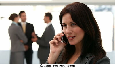Businesswoman on the phone while her team is working in the...
