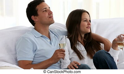 Couple drinking Champagne together sitting on the sofa