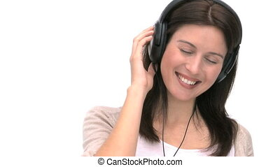 Closeup of a woman listening to music against a white...
