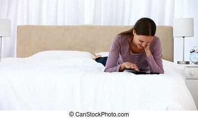 Smiling woman using a computer tablet lying on the bed at...