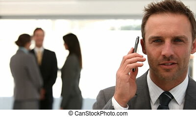 Businessman on the phone while her team is working in the...