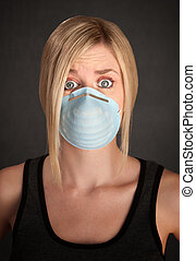 Surgical Mask Safety - Worried young blonde woman with...