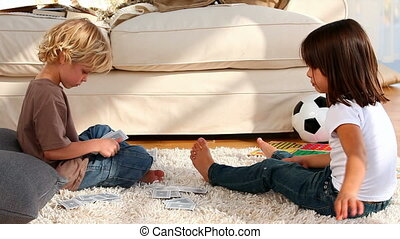 Boy and his siter playing cards while they are setting on...