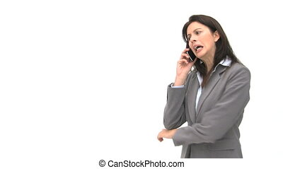 Annoyed businesswoman talking on the phone against a white...