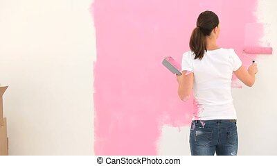 Young woman painting a wall and talking with her husband