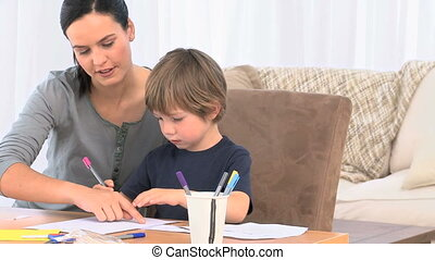Adorable mother helping her son to drawing in their living...