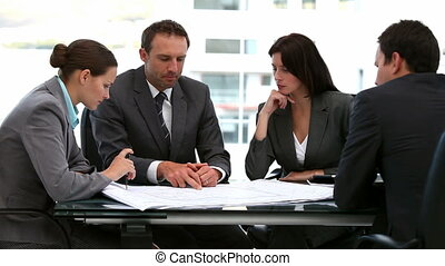 Businessmen and businesswomen working together on a document...