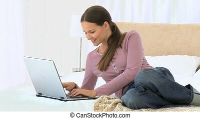 Lovely girl using at a laptop sitting on the bed at home
