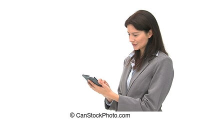 Serious businesswoman using a computer tablet against a...
