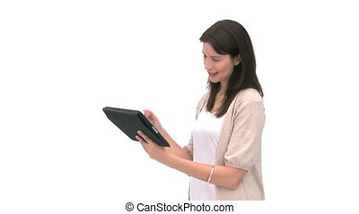 Smiling woman using a computer tablet against a white...
