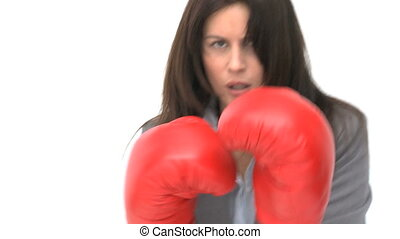 Serious businesswoman with boxing gloves against a white...