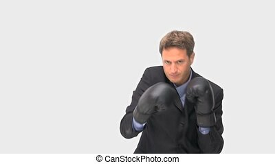 Businessman boxing towards the camera against a white...