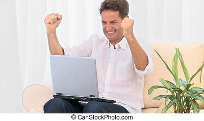 A very happy man with his laptop at home