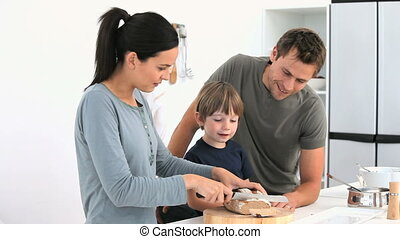 Adorable family cutting bread in the kitchen