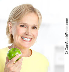 Woman with apple - Mature smiling woman with a green apple