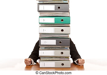 Desperate business woman sits behind folder stack. Isolated...