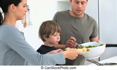 Man serving a salad to his family for lunch in the kitchen