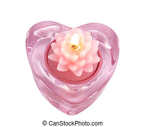 Aromatic candle lotus flower in a glass candlestick in the form of hearts, close-up on a white background