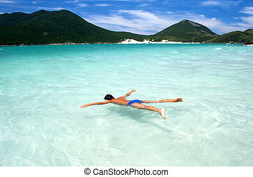 Swimming in crystalline clear waters in Arraial do Cabo, Rio...