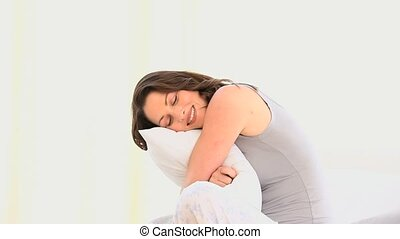 Gorgeous woman hugging her pillow against a white background