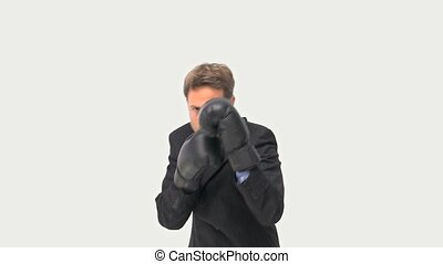 Serious businessman boxing towards the camera against a...