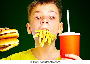 child and fast food - boy with meal in a mouth