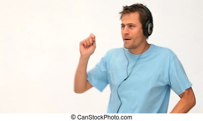 Man dancing and listening to music with headset against a...