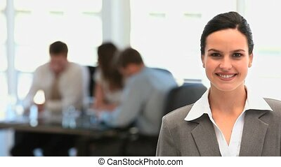 Businesswoman smiling at the camera while her team is...