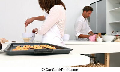 Little girl taking a fresh cookie in the kitchen