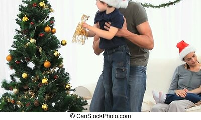 Father helping his son to decorate the Christmas tree...