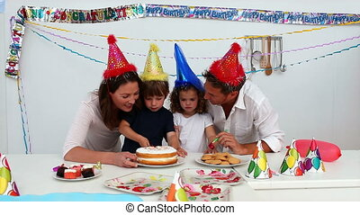 Boy cutting his birthday cake during a party at home