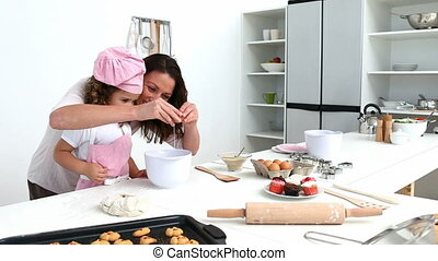 Mother and daughter preparing the dough for baking