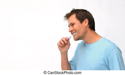 Handsome guy brushing his teeth against a white background