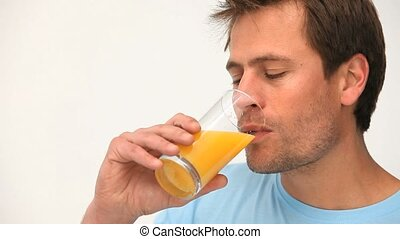 Man drinking a glass of orange juice against a white...