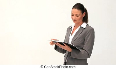 Businesswoman writting on a notepad against a white...