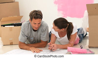 Couple looking at a plan for their room renovation - Couple...