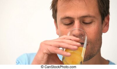 Man drinking orange juice against a white background