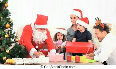 Santa Claus offering Christmas present to the mother in the...