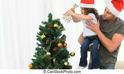 Father helping his daughter to decorate the Christmas tree...