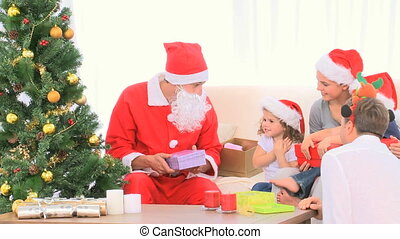 Santa Claus offering a Christmas gift to a boy - Santa Claus...