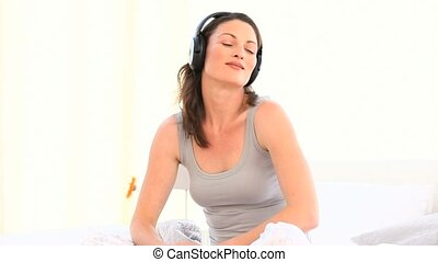 Woman listening to music in the bedroom