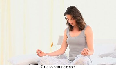 Woman doing yoga sitting on her bed