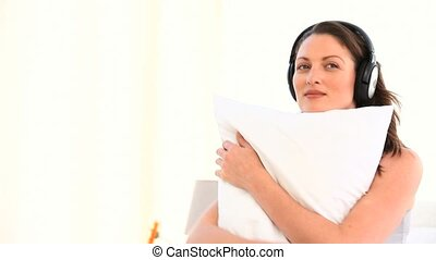 Woman hugging her pillow and listening to music in the...