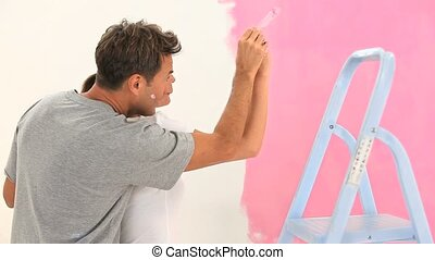Lovely couple painting a wall in pink during a renovation