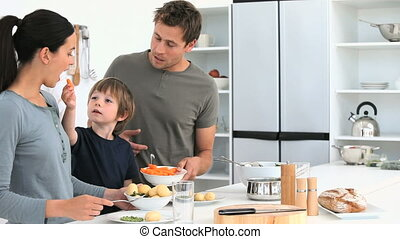 Family eating vegetables while they prepare lunch - Family...