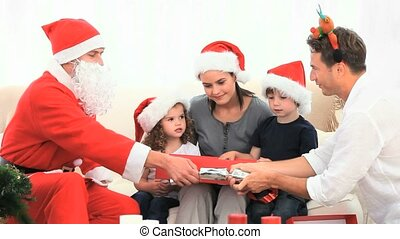 Family opening gift with Santa Claus in the livingroom