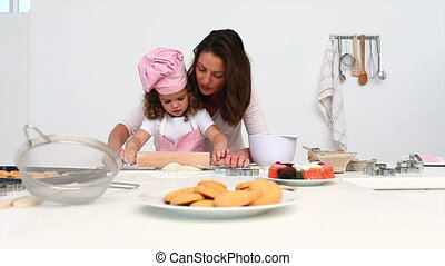 Mother and daughter rolling dough in the kitchen