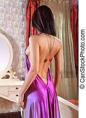 lady in the bedroom - beautiful young lady at mirror fits on...