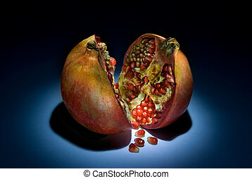 Fantastic pomegranate - Two parts of a pomegranate on a dark...