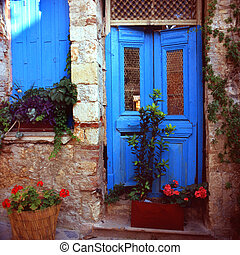 Door of a Greek ruin - A freshly painted, crumbling door and...